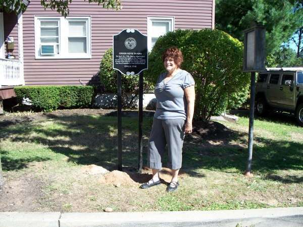 Person posing in front of historic marker